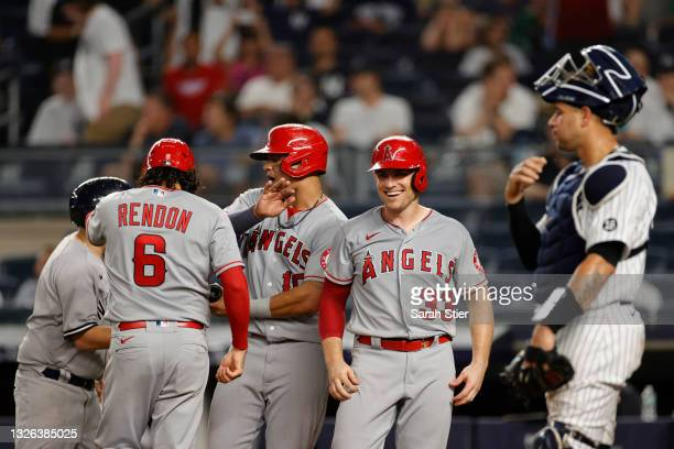 Anthony Rendon, Juan Lagares, and Max Stassi of the Los Angeles Angels celebrate after scoring on a grand slam to tied the game hit by Jared Walsh ,...