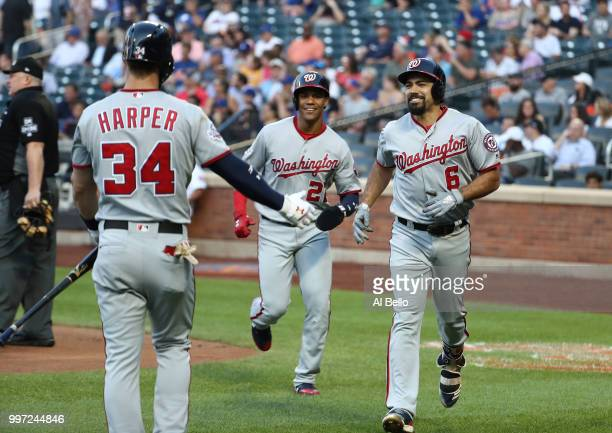 Anthony Rendon of the Washington Nationals celebrates his two run home run against the New York Mets in the first inning with Bryce Harper during...