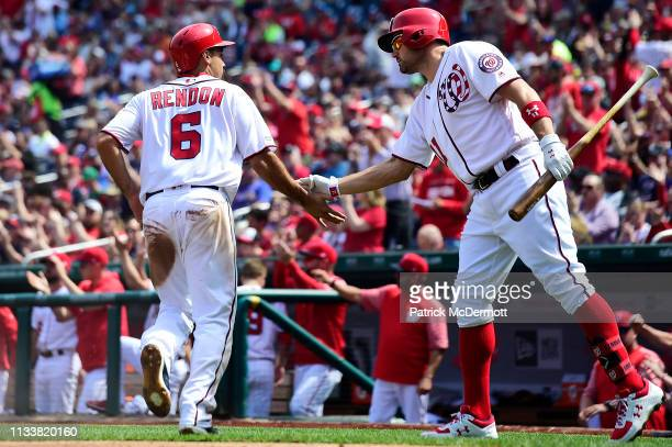 Anthony Rendon of the Washington Nationals celebrates with Ryan Zimmerman after scoring on an RBI single by Juan Soto in the first inning against the...