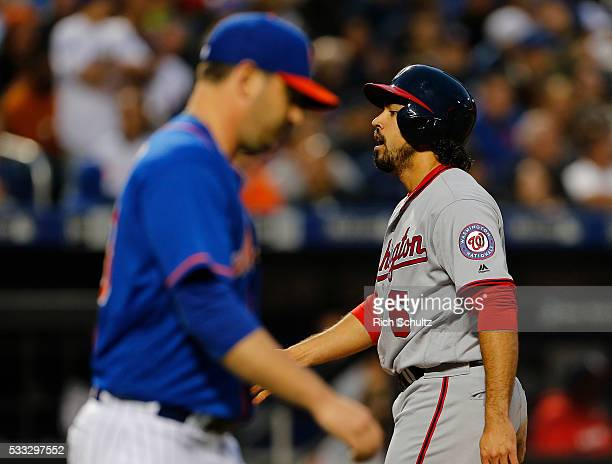 Anthony Rendon of the Washington Nationals crosses paths with pitcher Matt Harvey of the New York Mets after scoring on a single by Wilson Ramos...