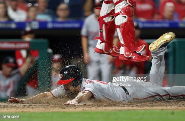 Anthony Rendon of the Washington Nationals scores as catcher Andrew Knapp of the Philadelphia Phillies jumps to catch a throw on a sacrifice fly by...