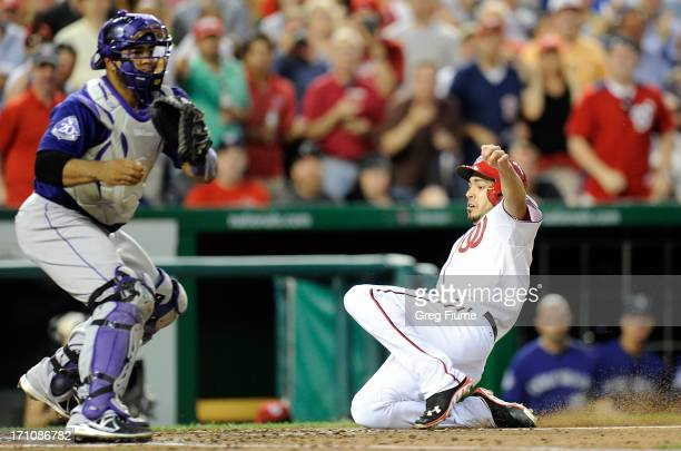 Anthony Rendon of the Washington Nationals scores in the sixth inning ahead of the throw to Wilin Rosario of the Colorado Rockies at Nationals Park...
