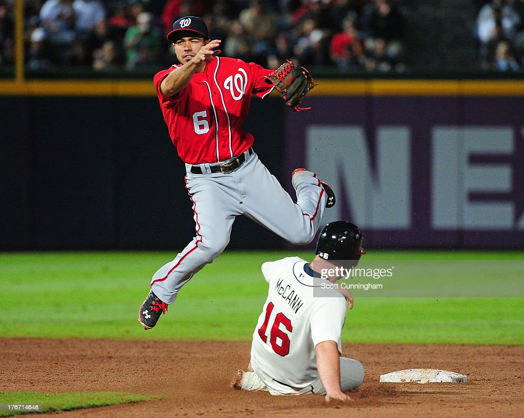 Anthony Rendon #6 of the Washington Nationals turns a double play against Brian McCann #16 of the Atlanta Braves at Turner Field on August 17, 2013 in Atlanta, Georgia.