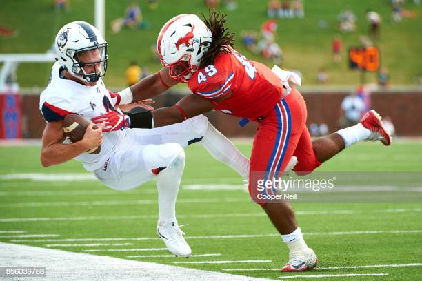 Anthony Rhone of the SMU Mustangs pushes Bryant Shirreffs of the Connecticut Huskies out of bounds during the second half at Gerald J Ford Stadium on...