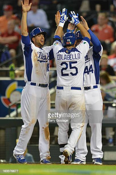 Anthony Rizzo and Alex Liddi of Team Italy greet teammate Chris Colabello at the plate after his threerun home run in the bottom of the third inning...