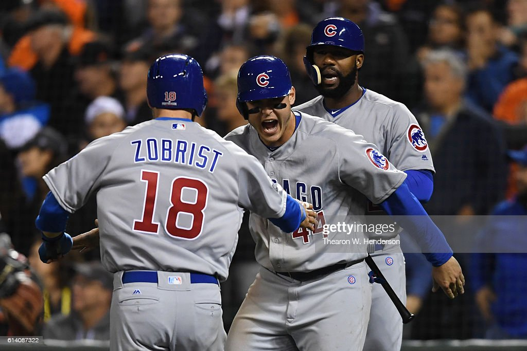 Anthony Rizzo #44 and Ben Zobrist #18 of the Chicago Cubs celebrate after scoring to tie during Game Four in the ninth inning on a single by Willson Contreras #40 in the National League Division Series against the San Francisco Giants at AT&T Park on October 11, 2016 in San Francisco, California.