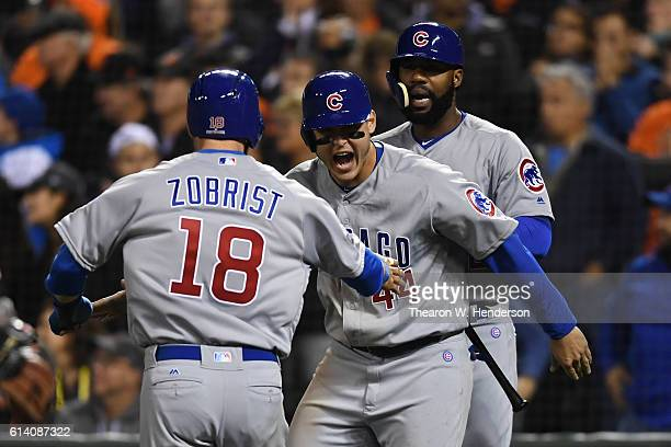 Anthony Rizzo and Ben Zobrist of the Chicago Cubs celebrate after scoring to tie during Game Four in the ninth inning on a single by Willson...