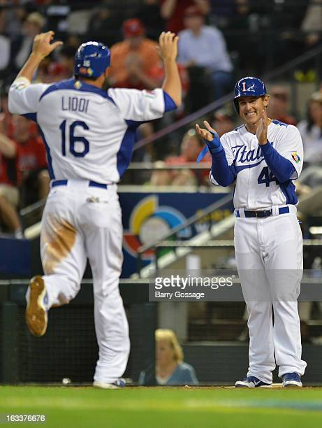 Anthony Rizzo of Team Italy greets teammate Alex Liddi at the plate in the bottom of the third inning of Pool D Game 2 between Team Canada and Team...