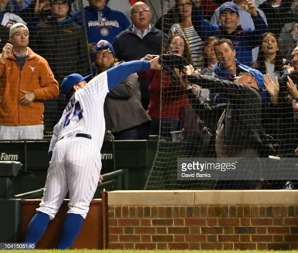 Anthony Rizzo of the Chicago Cubs and a fan attempt to catch a foul ball hit by Francisco Cervelli of the Pittsburgh Pirates during the ninth inning...