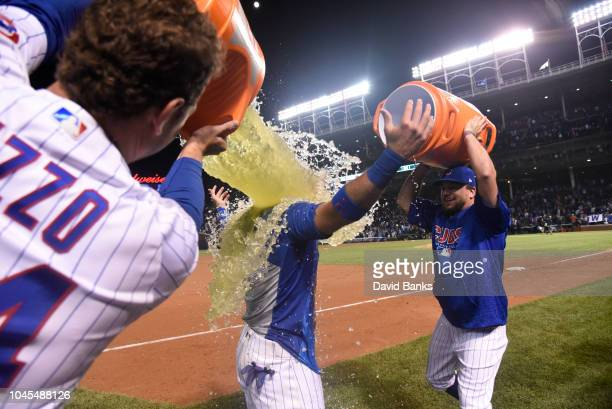 Anthony Rizzo of the Chicago Cubs and Kyle Schwarber pour gatorade on Albert Almora Jr of the Chicago Cubs after his gamewinning walkoff single...