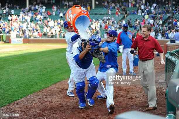 Anthony Rizzo of the Chicago Cubs and Matt Garza attack teammate Dioner Navarro with water and shaving cream as he is interviewed after the game...
