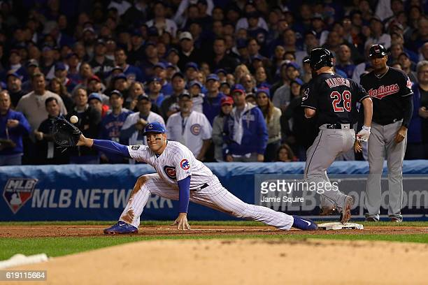 Anthony Rizzo of the Chicago Cubs attempts to catch a throw from Kris Bryant as Corey Kluber of the Cleveland Indians reaches first base for a single...