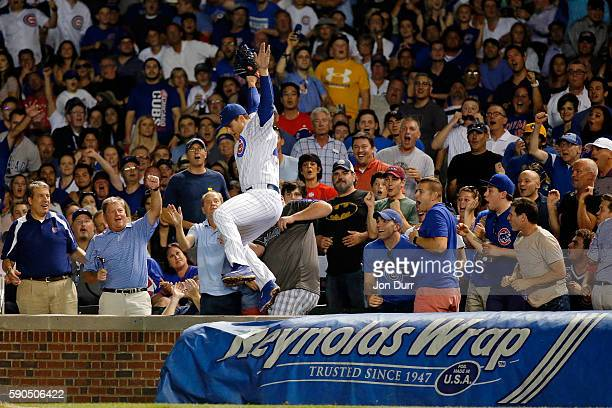 Anthony Rizzo of the Chicago Cubs celebrates after making a catch for an out against the Milwaukee Brewers while standing on the wall during the...