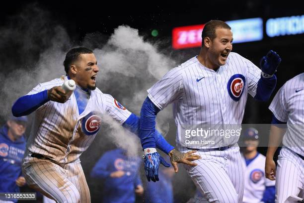 Anthony Rizzo of the Chicago Cubs celebrates his walk off single with Javier Baez and teammates of the Chicago Cubs in the 11th inning against the...