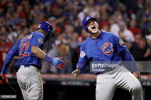 Anthony Rizzo of the Chicago Cubs celebrates with Jason Heyward after Rizzo scores a run in the 10th inning on a Miguel Montero against the Cleveland...