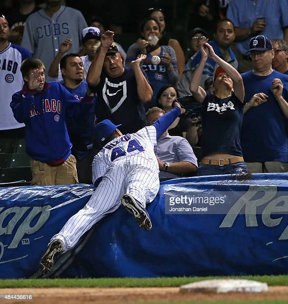 Anthony Rizzo of the Chicago Cubs dives over the tarp to try to catch a foul ball in the 3d inning against the Detroit Tigers at Wrigley Field on...