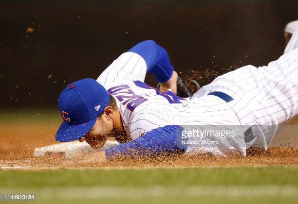 Anthony Rizzo of the Chicago Cubs dives to first base to get Cody Bellinger of the Los Angeles Dodgers out during the second inning of a game at...