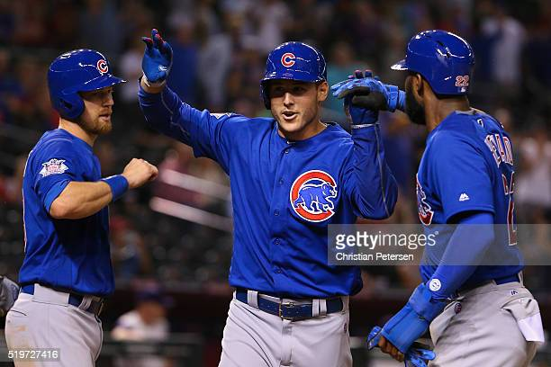 Anthony Rizzo of the Chicago Cubs high-fives Ben Zobrist and Jason Heyward after hitting a three-run home run against the Arizona Diamondbacks during...