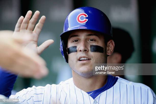 Anthony Rizzo of the Chicago Cubs is congratulated in the dugout after collecting the 1000th hit of his career a single in the 3rd inning against the...
