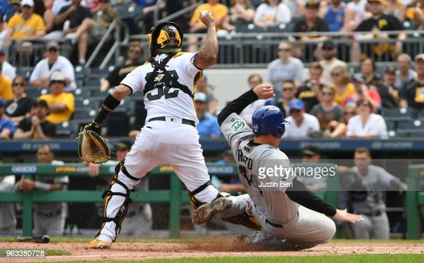 Anthony Rizzo of the Chicago Cubs is forced out at home plate as he slides into the feet of Elias Diaz of the Pittsburgh Pirates in the eighth inning...