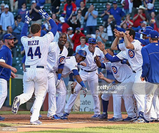 Anthony Rizzo of the Chicago Cubs is greeted by teammates after hitting a walkoff tworun home run in the 13th inning to beat the Miami Marlins at...