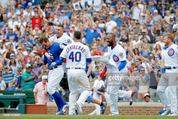 Anthony Rizzo of the Chicago Cubs is mobbed by Albert Almora Jr #5 Willson Contreras and Jason Heyward after hitting a walkoff home run in a win over...