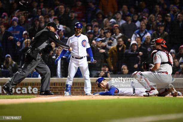 Anthony Rizzo of the Chicago Cubs is tagged out at home plate by JT Realmuto of the Philadelphia Phillies during a game at Wrigley Field on May 20...