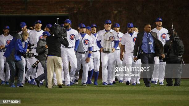 Anthony Rizzo of the Chicago Cubs leads the team onto the field with the World Series trophy before the home opening game between the Chicago Cubs...