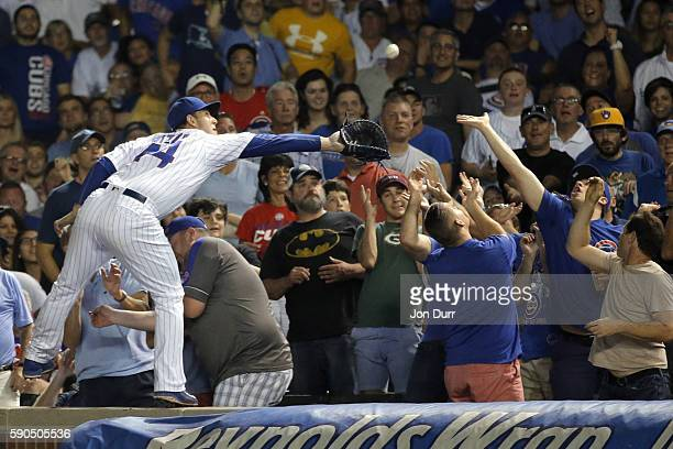 Anthony Rizzo of the Chicago Cubs makes a catch for an out against the Milwaukee Brewers while standing on the wall during the fifth inning in game...