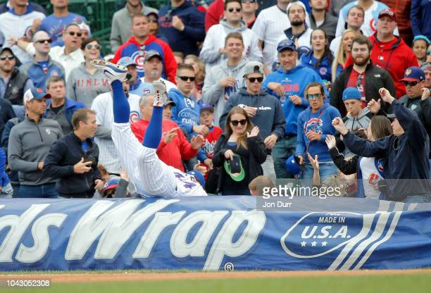 Anthony Rizzo of the Chicago Cubs reaches for a foul ball into the stands hit by Jose Martinez of the St Louis Cardinals during the eighth inning at...
