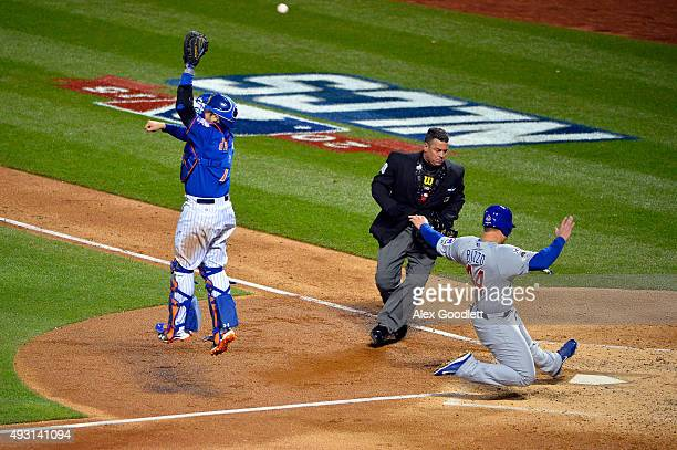 Anthony Rizzo of the Chicago Cubs scores a run in the fifth inning as Travis d'Arnaud of the New York Mets jumps to catch the throw from the outfield...