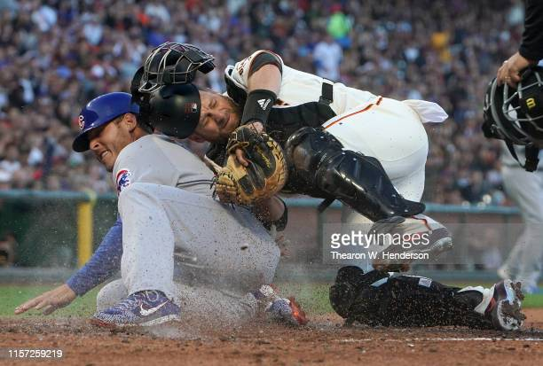 Anthony Rizzo of the Chicago Cubs scores while colliding with catcher Stephen Vogt of the San Francisco Giants in the top of the fourth inning at...