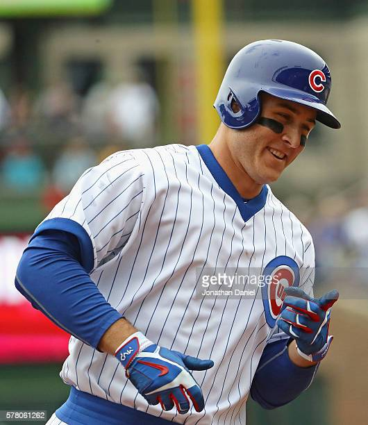 Anthony Rizzo of the Chicago Cubs smiles and points to the dugout as he runs the bases after hitting a solo home run in the 3rd inning against the...