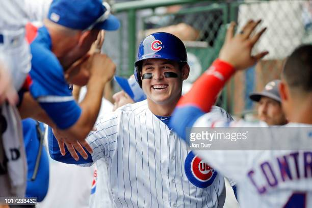 Anthony Rizzo of the Chicago Cubs smilies as he is congratulated in the dugout after hitting a two run home run against the Milwaukee Brewers during...