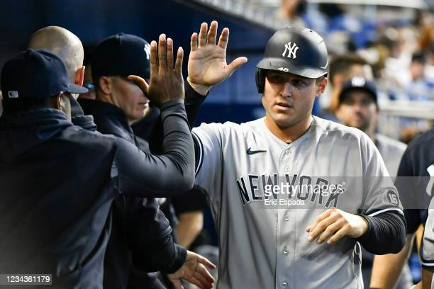 Anthony Rizzo of the New York Yankees is congratulated by teammates after scoring in the second inning against the Miami Marlins at loanDepot park on...