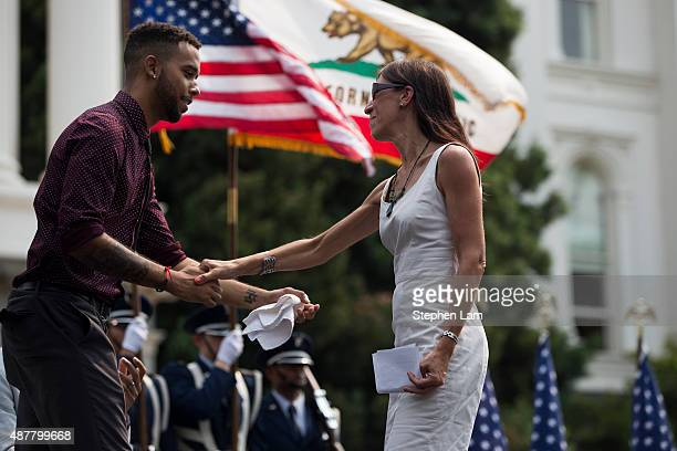 Anthony Sadler shakes hands with Pauline Carmona Consul General of France in San Francisco on stage during a parade honoring Sadler's August 21...