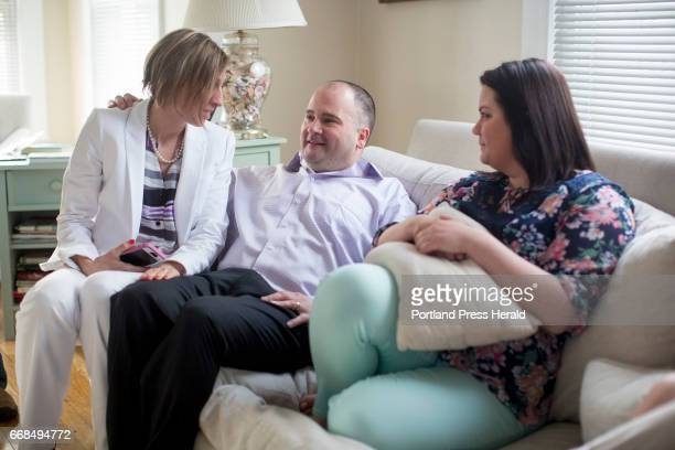 Anthony Sanborn sits on the couch of his friend Lisa Alexander's home with his wife Michelle Sanborn at left and his daughter Santana Levier about a...