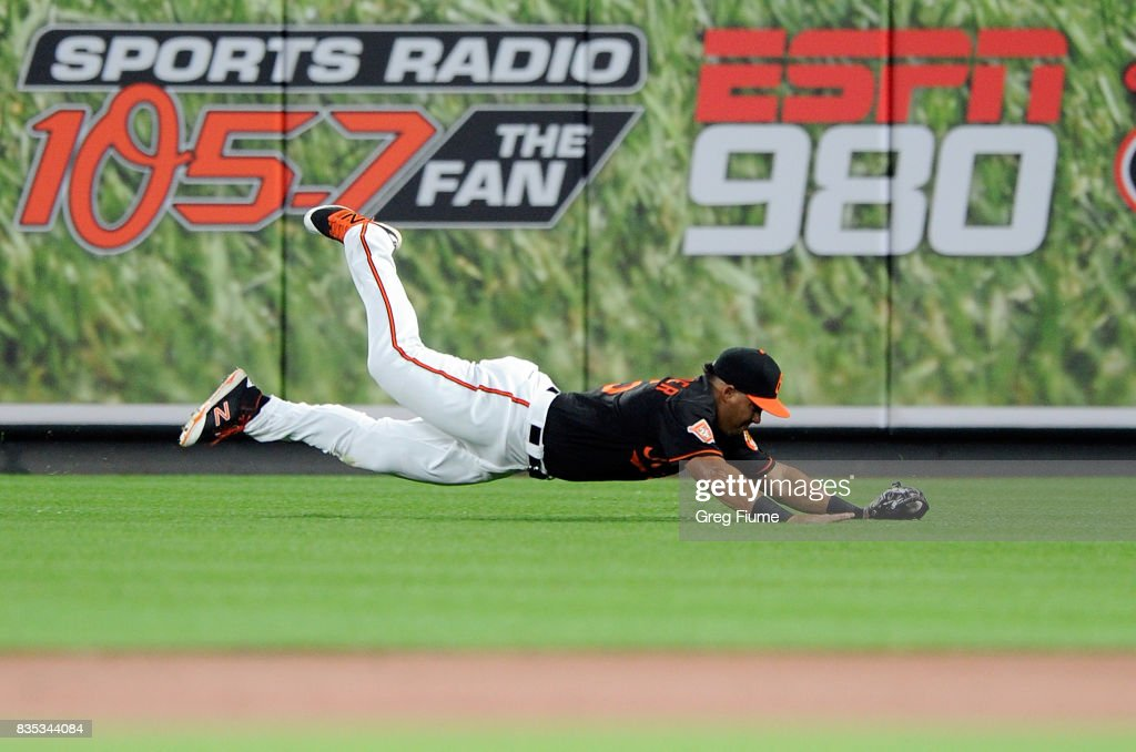 Anthony Santander #25 of the Baltimore Orioles makes a diving catch during his major league debut in the second inning against Mike Trout #27 (not pictured) of the Los Angeles Angels at Oriole Park at Camden Yards on August 18, 2017 in Baltimore, Maryland.