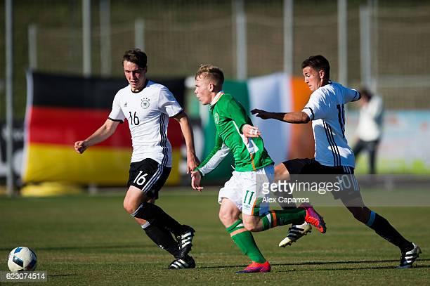 Anthony Scully of Ireland conducts the ball between Adrian Fein and Romario Rosch of Germany during the U18 international friendly match between...
