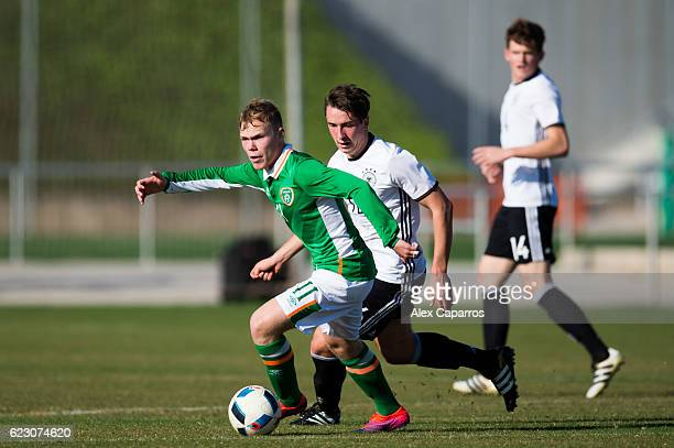 Anthony Scully of Ireland conducts the ball next to Adrian Fein of Germany during the U18 international friendly match between Ireland and Germany on...