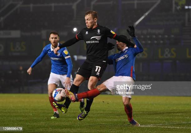 Anthony Scully of Lincoln City is challenged by Ryan Williams of Portsmouth FC during the Sky Bet League One match between Portsmouth and Lincoln...