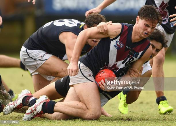 Anthony Seaton of the Dragons handballs whilst being tackled during the round one TAC Cup match between Northern Knights and Sandringham at Frankston...