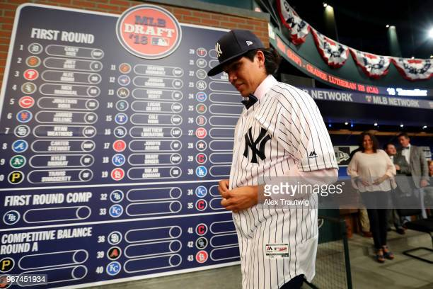 Anthony Seigler puts on the hat and jersey of the New York Yankees after being selected 23rd overall by the Yankees during the 2018 Major League...