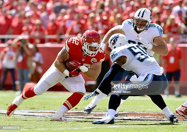 Anthony Sherman of the Kansas City Chiefs runs the ball against Zaviar Gooden of the Tennessee Titans during the first quarter at Arrowhead Stadium...