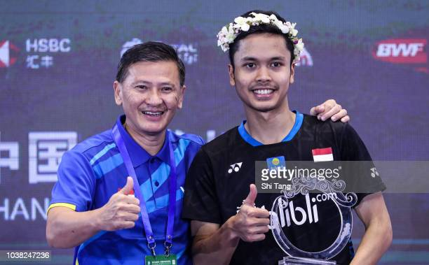 Anthony Sinisuka Ginting of Indonesia and his coach Hendry Saputra Ho pose with the trophy after the Men's Single final match on day six of the China...