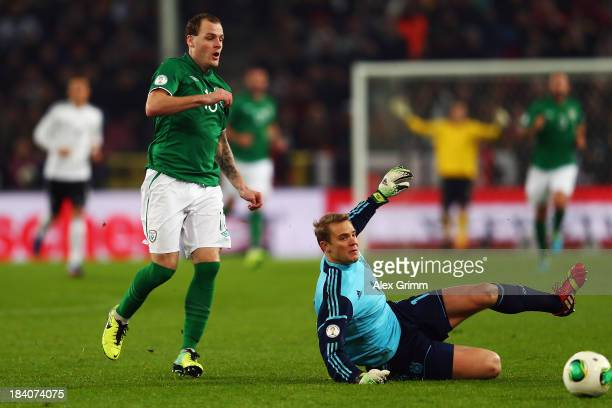Anthony Stokes of Ireland is challenged by goalkeeper Manuel Neuer of Germany during the FIFA 2014 World Cup Group C qualifiying match between...