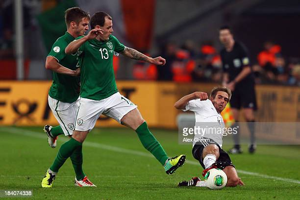 Anthony Stokes of Ireland is challenged by Philipp Lahm of Germany during the FIFA 2014 World Cup Group C qualifiying match between Germany and...