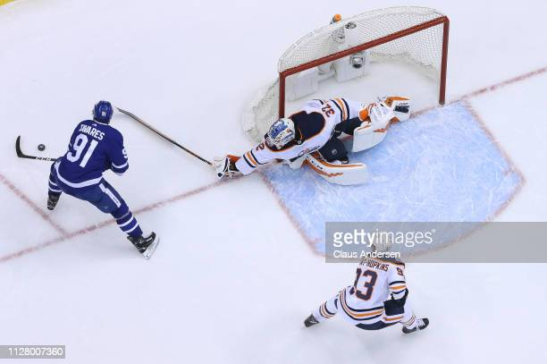 Anthony Stolarz of the Edmonton Oilers tries to check John Tavares of the Toronto Maple Leafs during an NHL game at Scotiabank Arena on February 27...