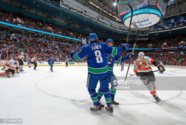 Anthony Stolarz of the Philadelphia Flyers looks on dejected as Christopher Tanev of the Vancouver Canucks is congratulated by teammates after...