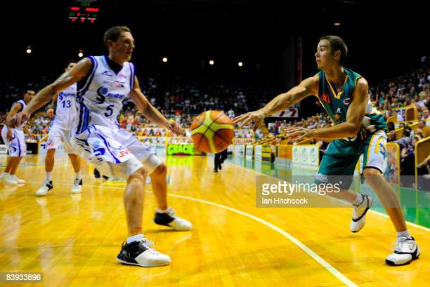 Anthony Susnjara of the Crocodiles s gets a pass away past Graeme Dann of the Spirit during the round 12 NBL match between the Townsville Crocodiles...